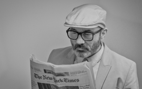 Man reading newspaper with glasses